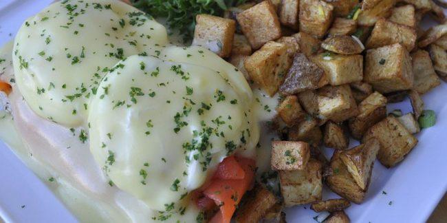 Huevos estrellados sobre salmón y pan artesanal acompañado de papas y ensalada de frutas de Le Fun en Bouche.