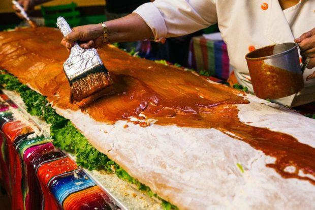 Bañando el pambazo con salsa de chile guajillo.