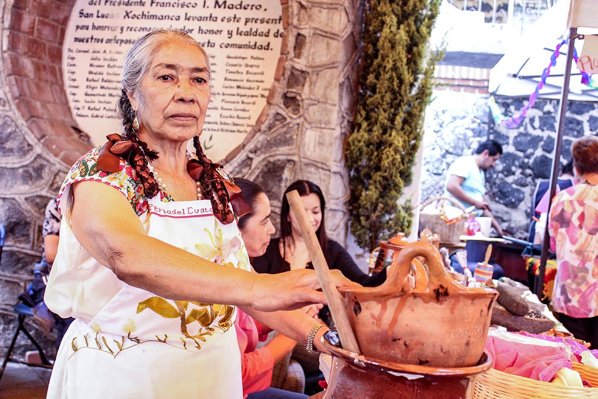 Eleuteria Romero Contreras junto a una olla de sus frijoles cuatatapa durante la Muestra Gastronómica y Cultural Cuatatapa 2017 el 23 de abril en el pueblo de San Lucas Xochimanca.