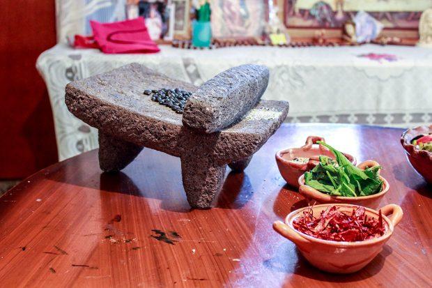 En la casa de Romero Contreras en San Lucas Xochimanca, frijoles negros esperan ser triturados en un metate, un tipo de mortero hecho de roca volcánica tallada. En las cazuelas más abajo, chiles (al frente), epazote y los frijoles triturados están listos para ser cocinados. Foto: Mayela Sánchez, GPJ Mexico. prehispánicos
