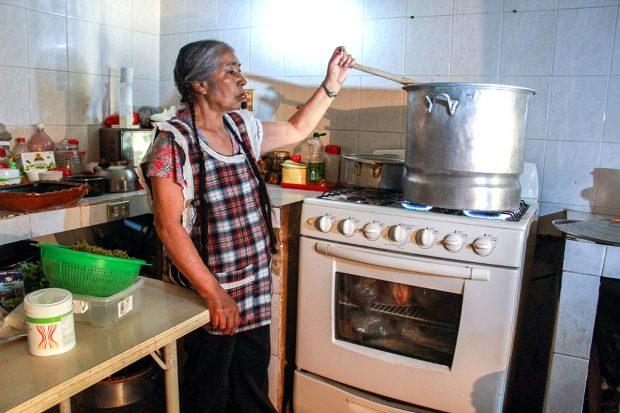 Romero Contreras prepara frijoles cuatatapa en su cocina. Cuando prepara el plato para su familia usualmente solo usa la mitad de las cantidades de la receta y usa una olla de barro, pero para la cantidad de guiso que está preparando para el festival se necesitan grandes porciones y una olla grande de aluminio. FOTO: Mayela Sánchez, GPJ Mexico.